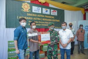 Aster Kakostrad, Heri Susanto (kedua kanan) turut membantu memberikan paket sembako dari Asuransi Astra kepada perwakilan warga yang hadir.